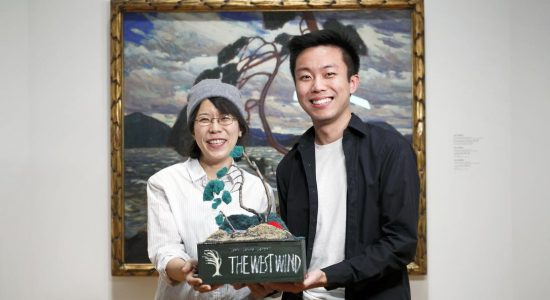 Rachel Han (left) and Norbert Zhao, OCAD university graduate students of the Inclusive Design program, stand alongside Tom Thomson's The West Wind at the Art Gallery of Ontario holding their multi-sensory interpretive project.