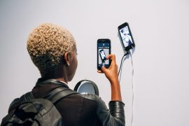 Woman photographing an artwork with her iPhone.