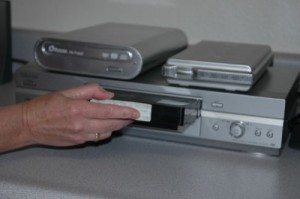Hand putting in a vhs tape into a vhs player