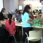 photo of people gathered around a table, preparing pop bottles