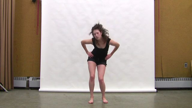 Still from video; shows woman in exercise-style clothing dancing in a studio with a white a sheet hung behind her