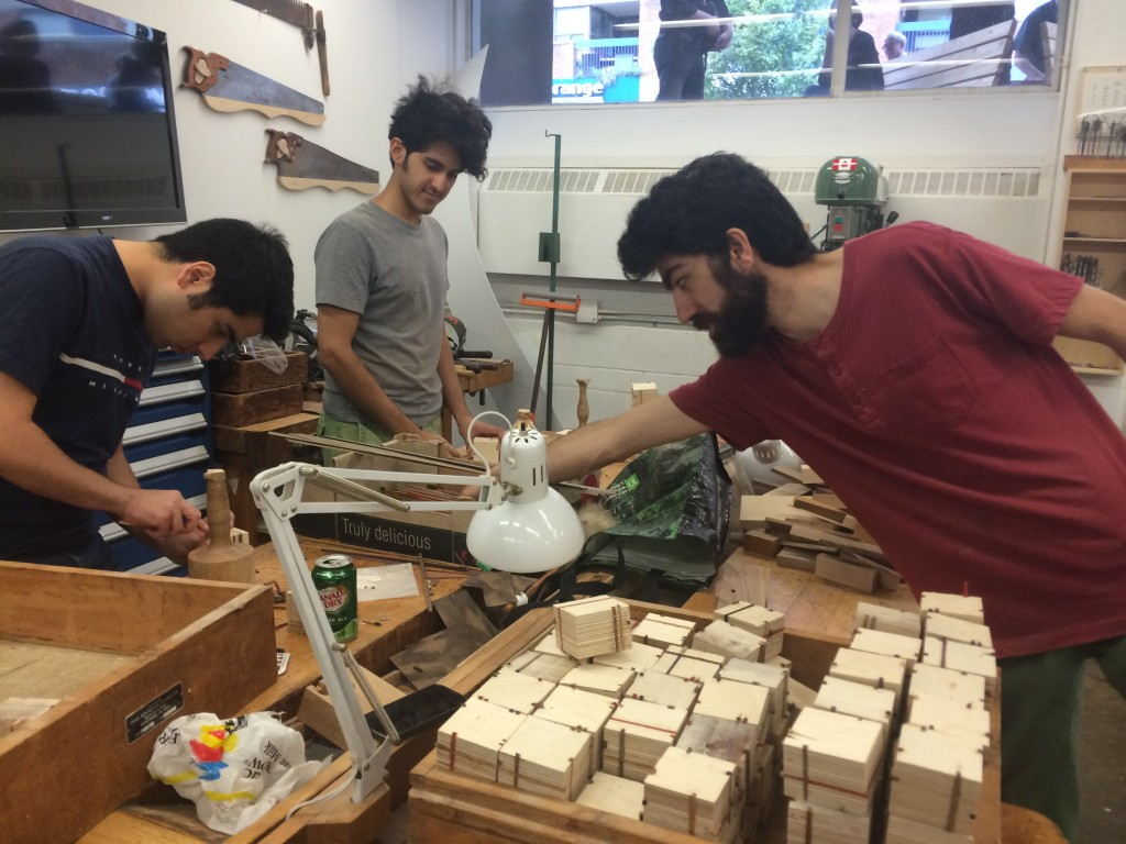 three students in the OCAD U Wood Shop creating wooden sculptural pieces