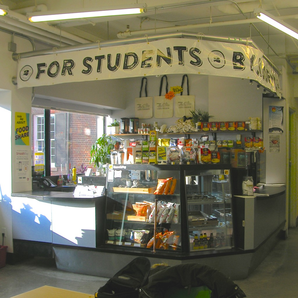 [Image description: photo of the cafe counter, showcasing food options available for sale and a sign above the counter stating 'For Students By Students']