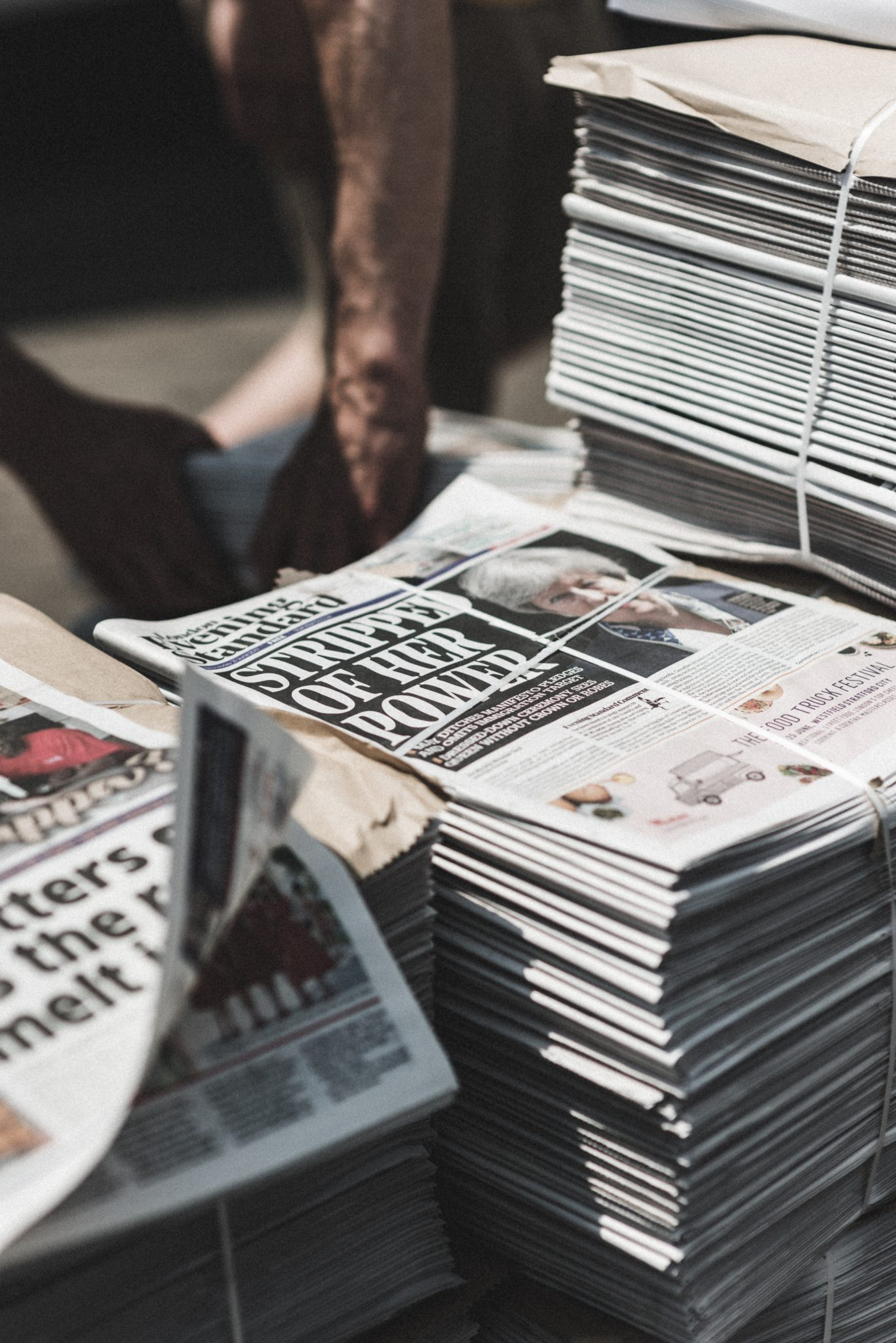 Shallow focus photography of piles of newspapers, photography by