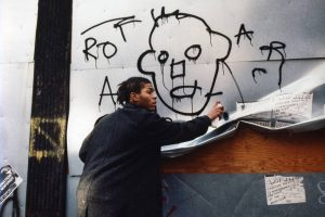 Figure 5. Jean-Michel Basquiat executing one of his street art work in the 80s. (Source: https://www.widewalls.ch/street-art-legends-best-of-basquiat-art/)