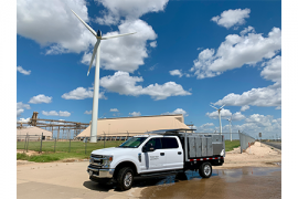 Photograph of Land Art Support Vehicle in front of a wind turbine and expansive blue sky with fluffy white clouds.